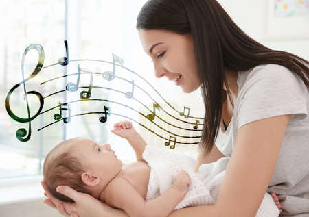 Mother with baby at home. Lullaby songs and music concept Stock Photo