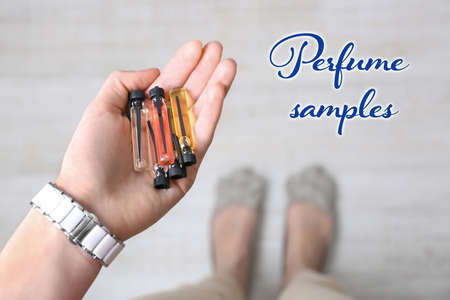 Woman holding perfume samples in hand Stock Photo