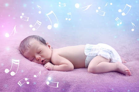Cute baby sleeping on plaid. Lullaby songs and music concept Stock Photo