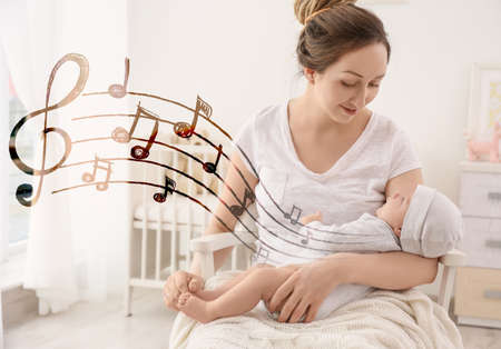 Mother with baby at home. Lullaby songs and music concept Imagens