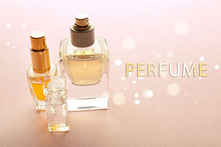 Bottles of perfume and text on color background