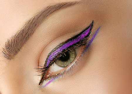 Female eye with lilac makeup, closeup