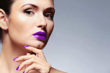 Young woman with beautiful lilac makeup on gray background