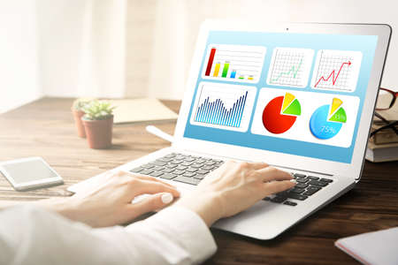 Marketing concept. Woman working with laptop in office. Schedule of income and business information on screen