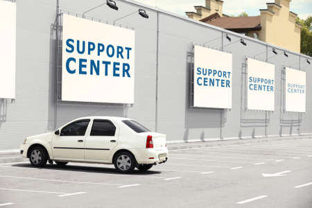 Car parked near office. Text SUPPORT CENTER on banners