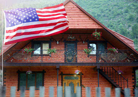 Waving USA flag in front of house