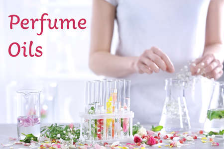 Perfume oils concept. Test tubes with infused floral water and woman on background