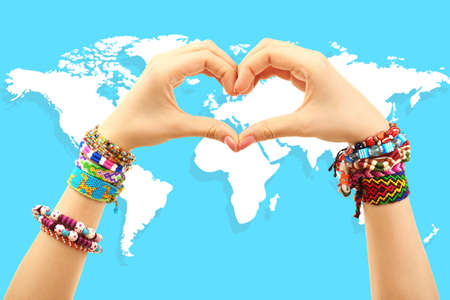 Woman holding hands in heart shape and world map on background. Earth concept