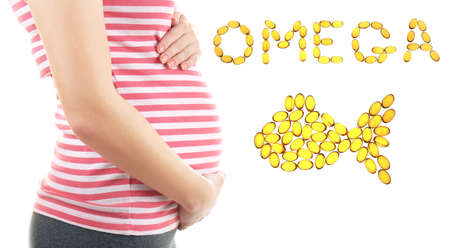 Concept of healthy pregnancy and fish oil. Pregnant woman and capsules on white background