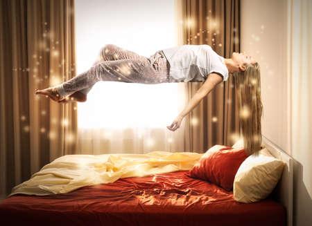 Concepto de parálisis del sueño. Mujer joven levitando sobre la cama Foto de archivo