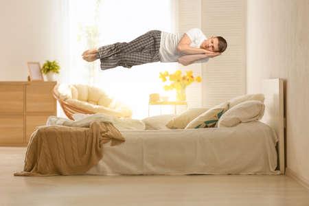 Schlaflähmungskonzept. Junger Mann, der über Bett schwebt