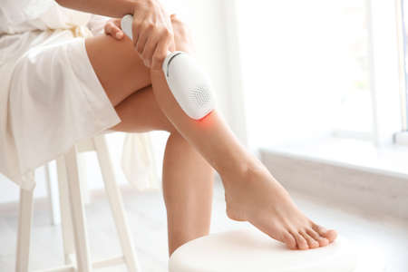 Beauty and skin care concept. Woman using laser epilator for hair removal procedure at home