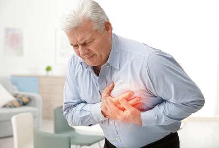 Concetto di attacco di cuore. Uomo maggiore che soffre di dolore toracico indoor