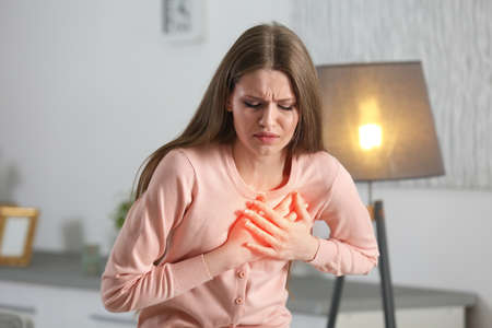 Heart attack concept. Woman suffering from chest pain indoor