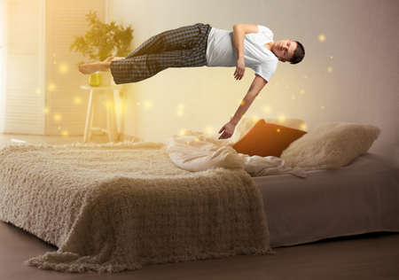 Sleep paralysis concept. Young man levitating over bed