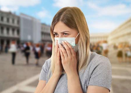 Gezondheidszorg concept. Jonge vrouw in gezichtsmasker op stadsstraat
