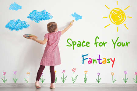 Art concept. Cute little girl drawing on white wall with space for design