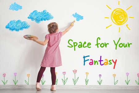 Kunstkonzept . Nettes kleines Mädchen Zeichnung auf weißer Wand mit Platz für Design