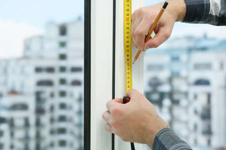 Young man taking measure of window for blinds installation at home