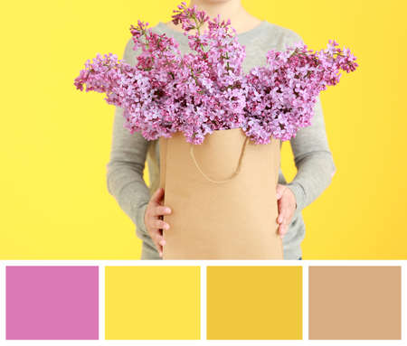 Color matching palette. Woman holding lilac flowers in paper bag on yellow background