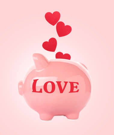 Piggy bank and heart on color background Stock Photo