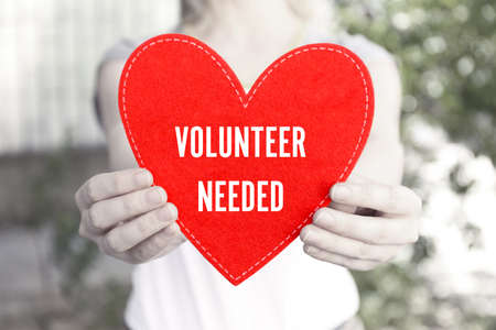 Woman holding red heart with text VOLUNTEER NEEDED, closeup. Concept of support and help