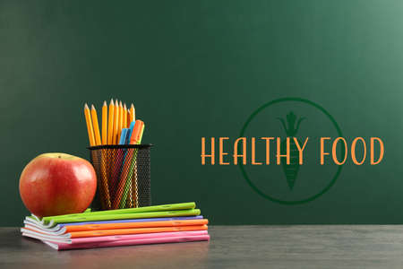 Apple and school stationery on table. Text HEALTHY FOOD on chalkboard Stock Photo