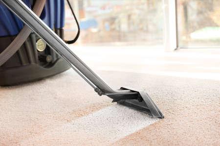 Schoonmaak service concept. Stoomdampreiniger die vuil van tapijt in vlakke, close-up% 00 verwijdert Stockfoto
