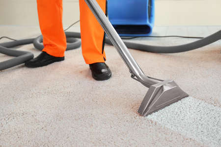 Cleaning service concept. Dry cleaners employee removing dirt from carpet in flat, closeup