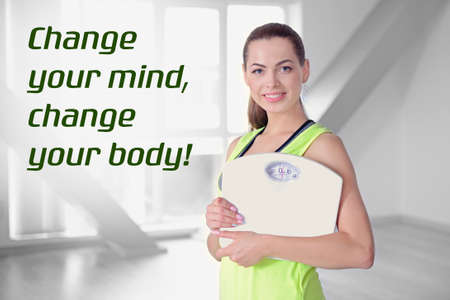 Weight loss motivation concept. Young woman holding scales at home. Text CHANGE YOUR BODY, CHANGE YOUR MIND on background
