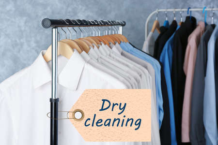 Concept of dry cleaning service. Hangers with clean clothes hanging on rack