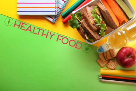 School lunch, stationery and text HEALTHY FOOD on colorful background