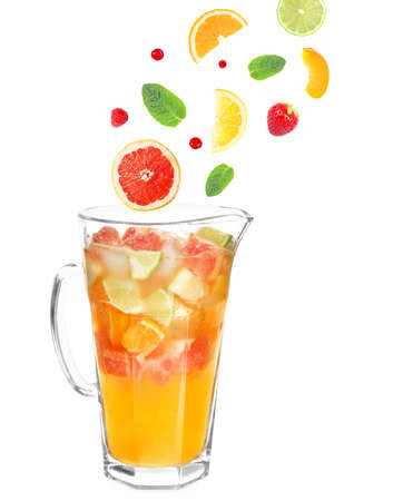 Falling fruit slices into glass jug with lemonade on white falling fruit slices and berries into glass jug with lemonade on white background recipe for forumfinder Gallery