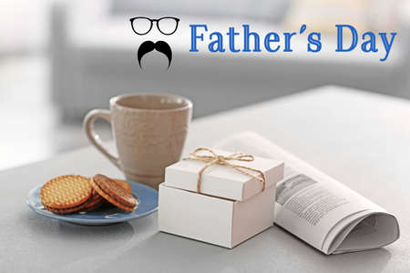 Breakfast with gift box and newspaper on table. Text HAPPY FATHERS DAY on background Stock Photo