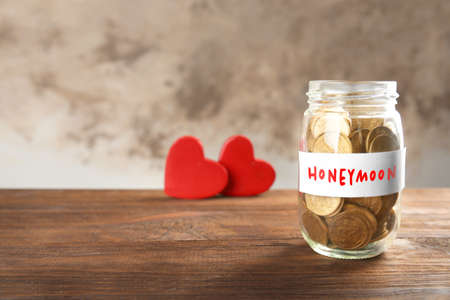 Money savings for honeymoon in glass jar on blurred background