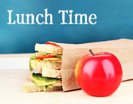 Lunch time concept. Tasty sandwiches in paper bag and apple on wooden table at classroom