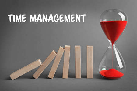 Time management concept. Hourglass and dominoes on gray background