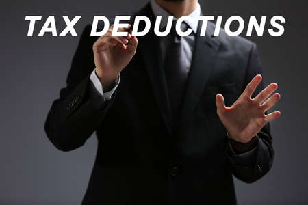 Man pointing on text TAX DEDUCTIONS against gray background Reklamní fotografie