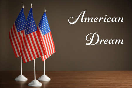 Text AMERICAN DREAM and USA flags on color background