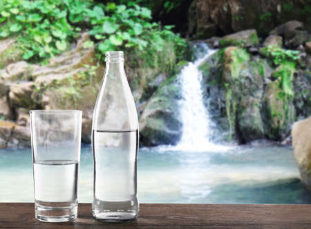 Glass and bottle of clear water on landscape background Banco de Imagens - 91915720