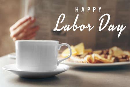 Kopje koffie en ontbijt op tafel. Tekst GELUKKIGE ARBEIDDAG op onscherpe achtergrond% 00 Stockfoto