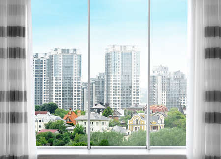 Cityscape view through modern window in room Stock Photo