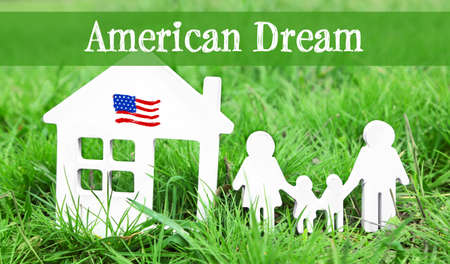 Text AMERICAN DREAM with models of house and family on green grass, closeup Stock Photo