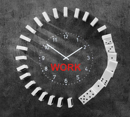 Falling dominoes around clock face on gray background. Concept of work time