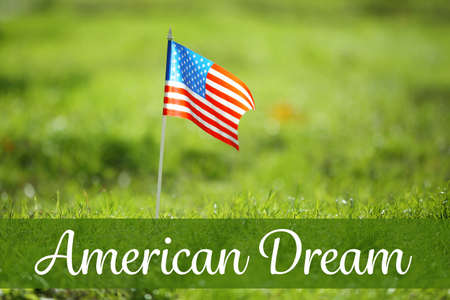 Text AMERICAN DREAM and USA flag on green grass, closeup