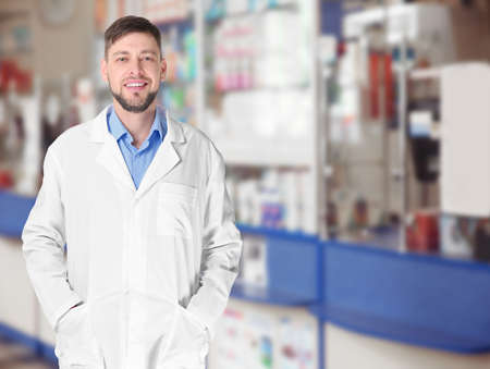 Male pharmacist at work. Blurred shelves with pharmaceutical products on background 版權商用圖片