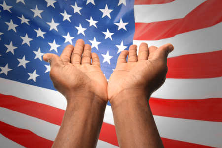 Male hands and American flag on background. Patriotic concept Stock Photo