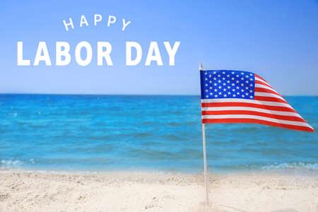 Bandiera americana sulla spiaggia. Testo FELICE GIORNO DEL LAVORO sullo sfondo% 00