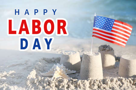 Sand castle with American flag on beach. Text HAPPY LABOUR DAY on background