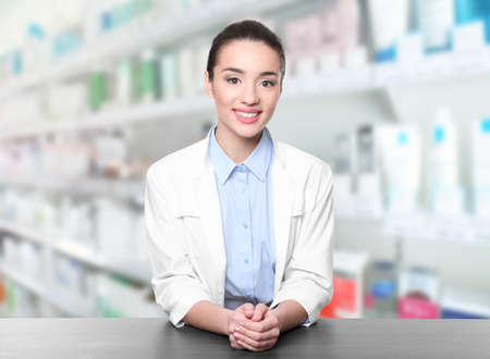 Young female pharmacist near counter at work. Blurred shelves with pharmaceutical products on background
